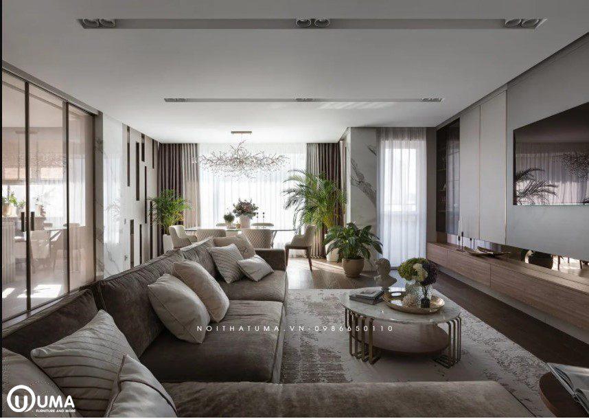 Phòng khách được trang bị bởi bộ sofa nỉ àu nâu xám, cùng chiếc bàn tròn nhỏ