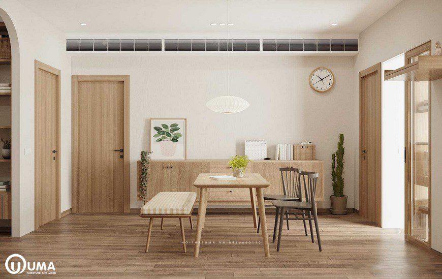 Chiếc bàn ăn được đặt giữa phòng, 1 bên là chiếc ghế băng có đệm kẻ trắng
