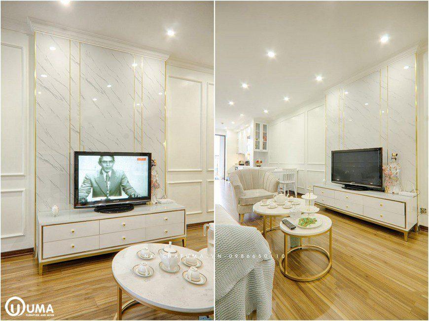 Kệ tivi cũng được tạo ra điểm nhấn với các đường chỉ kẻ vàng, kết hợp với các cánh tủ màu trắng