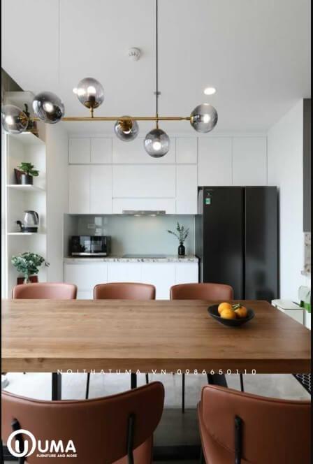 Bàn ăn được thiết kế ngay giữa không gian, giúp ngăn giữa phòng bếp và không gian phòng khách