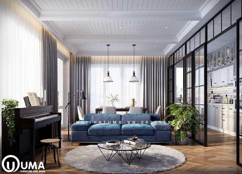 Phòng khách được trang trí với bộ sofa màu xanh, cùng chiếc bàn tròn trên chiếc thảm lông màu lông chuột ở giữa