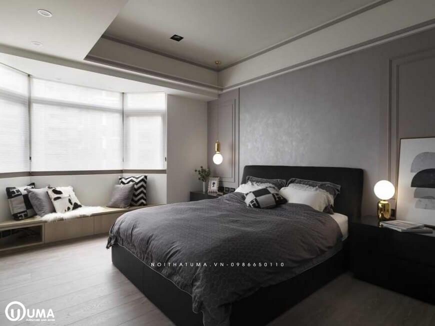 Chiếc giường ngủ được sử dụng với bộ chăn ga gối đệm màu nâu xám đặt giữa phòng